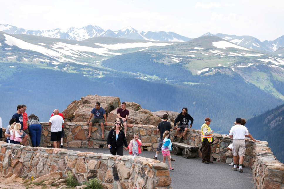 FILE - In this July 14, 2014 file photo, visitors take in a scenic overlook off Trail Ridge Road, above tree-line at Rocky Mountain National Park, near Estes Park, Colo. Visitation to America's national parks has set new records for three consecutive years. (AP Photo/Brennan Linsley, file)