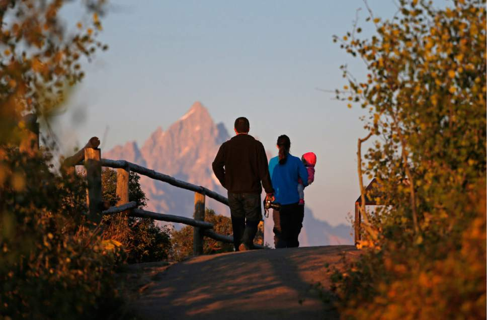 FILE - In this Aug 25, 2016 file photo, on the 100th anniversary of the National Park Service, visitors stroll with their baby as the sun at dawn illuminates mountain peaks as seen from Signal Mountain in Grand Teton National Park, Wyo. Visitation to America's national parks has set new records for three consecutive years. (AP Photo/Brennan Linsley, file)