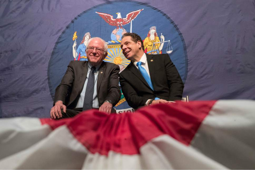 FILE- In this Jan. 3, 2017, file photo, New York Gov. Andrew Cuomo, right, and Vermont Sen. Bernie Sanders appear onstage together during an event at LaGuardia Community College in New York. Gov. Cuomo announced a proposal for free tuition at state colleges to hundreds of thousands of low- and middle income residents. (AP Photo/Mary Altaffer, File)