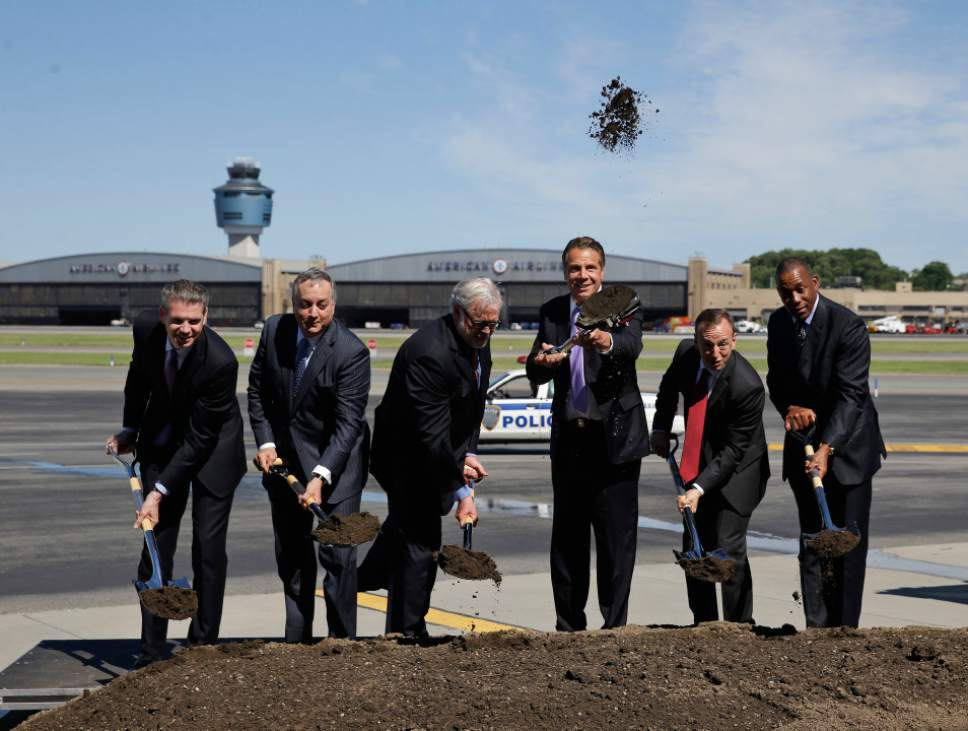 FILE- In this June 14, 2016 file photo, New York Gov. Andrew Cuomo, third from right, throws dirt in the air during a ceremonial ground breaking on the tarmac at LaGuardia Airport in New York. An ambitious Democratic governor with possible White House aspirations has a formula for staying blue in the time of Trump: Take your progressive message directly to angst-ridden middle-class voters. But some wonder just how sincere Cuomo really is, questioning whether his middle-class outreach formula that he defiantly posed as an alternative to Donald Trump is nothing more than the groundwork for a presidential run. And they question where this formula -- combining progressive social programs and big spending on airports, train stations and water infrastructure -- was during Cuomo's previous six years as governor. (AP Photo/Seth Wenig, File)