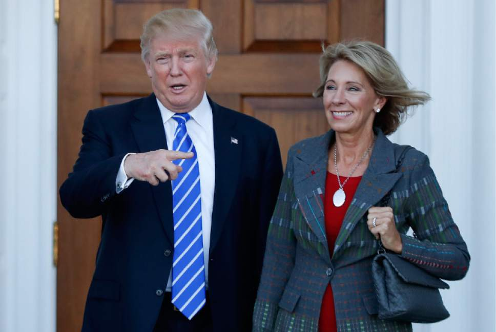 FILE - In this Nov. 19, 2016 file photo, President-elect Donald Trump stands with Education Secretary-designate Betsy DeVos in Bedminster, N.J. Charter school advocate and wealthy Republican donor Betsy DeVos is widely expected to push for expanding school choice programs if confirmed as education secretary, causing outrage among teachers' unions. But Democrats and rights activists also are raising concerns about how her conservative Christian beliefs and advocacy for family values might impact minority and LGBT students. (AP Photo/Carolyn Kaster, File)