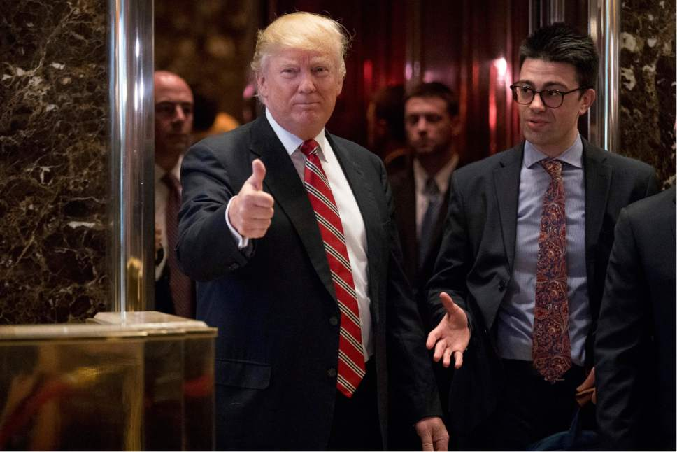 President-elect Donald Trump gives a thumbs up to members of the media after meeting with Martin Luther King III, son of Martin Luther King Jr., at Trump Tower in New York, Monday, Jan. 16, 2017. (AP Photo/Andrew Harnik)