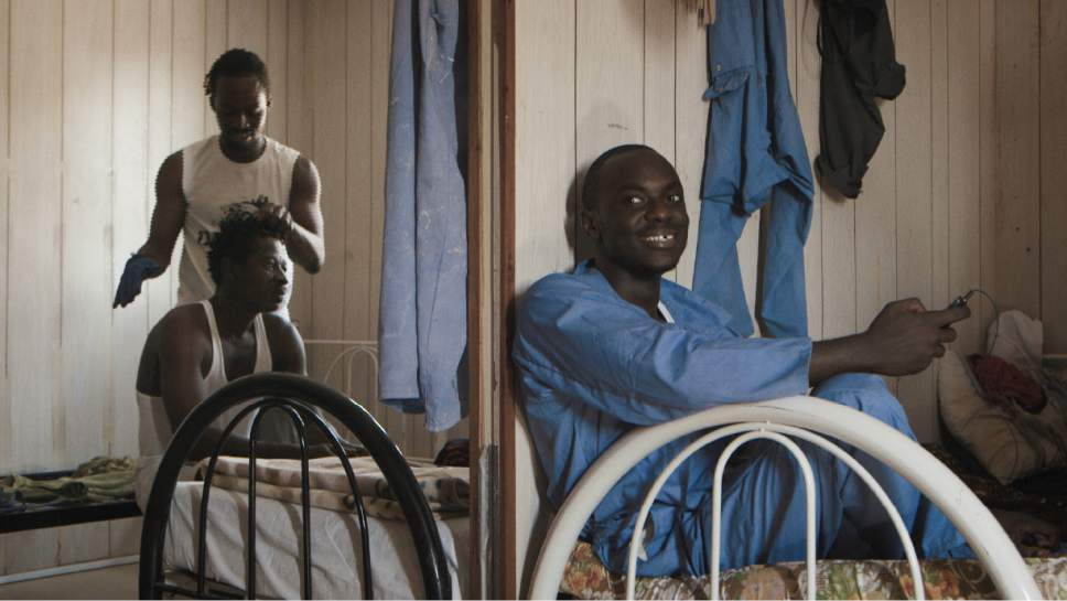 """Samuel from Ghana dreads his colleague's hair, with Calton from Kenya at the Um Salal camp on the outskirts of Doha, Qatar in a scene from """"The Workers Cup,"""" directed by Adam Sobel. Courtesy  
