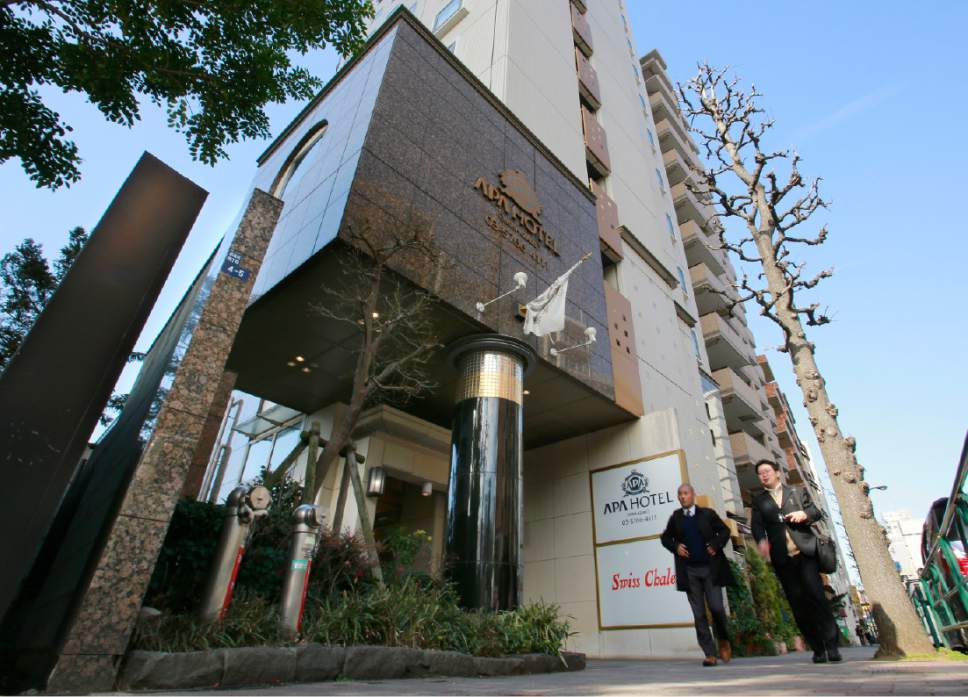 Men walk past an Apa Hotel in Tokyo, Wednesday, Jan. 18, 2017. The fast-growing Japanese hotel chain is facing criticism over a book penned by the hotel's owner that says the Rape of Nanking was fabricated. APA Group, a Tokyo-based land developer and operator of 400-plus hotels, drew fire for spreading the revisionist views of company president Toshio Motoya by putting the books in hotel guestrooms and also selling them. (AP Photo/Shizuo Kambayashi)