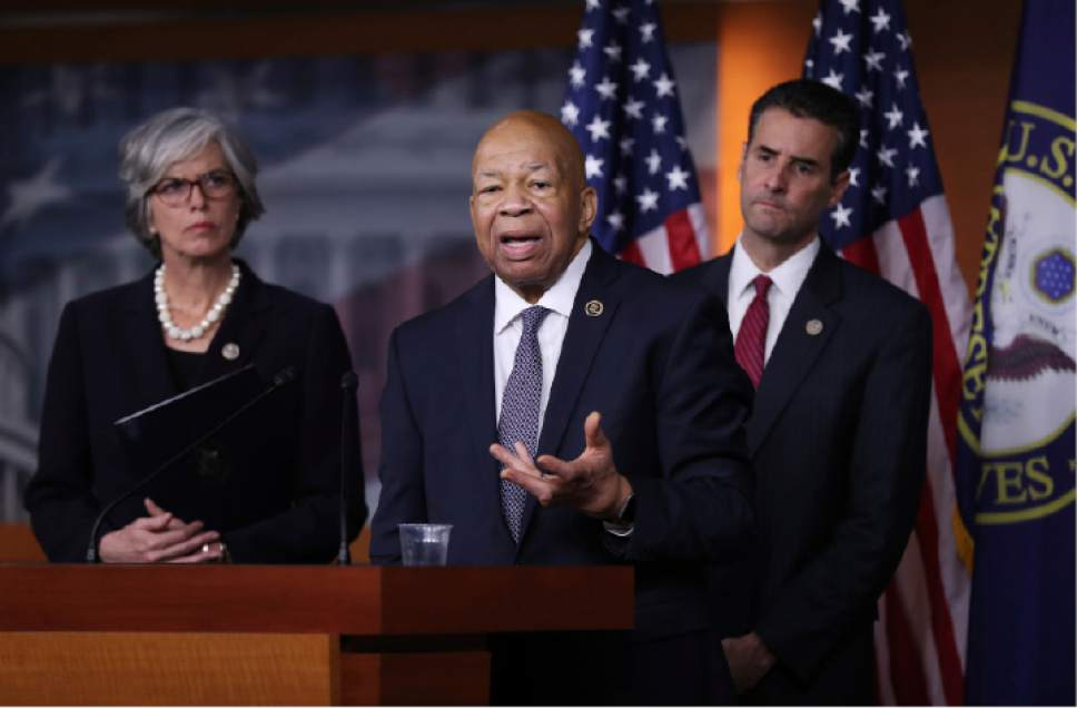 Rep. Elijah Cummings, D-Md., center, accompanied by Rep. John Sarbanes, D-Md., right, and Rep. Katherine Clark, D-Mass., speaks during a news conference on Capitol Hill in Washington, Thursday, Jan. 12, 2017 to discuss President-elect Donald Trump's conflicts of interest and ethical issues. (AP Photo/Manuel Balce Ceneta)