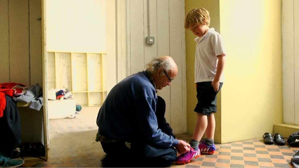 "Headfort School teacher John Leyden ties a  student's shoelaces in a scene from  ""In Loco Parentis,"" directed by Naesa Ní  Chianáin. Courtesy  