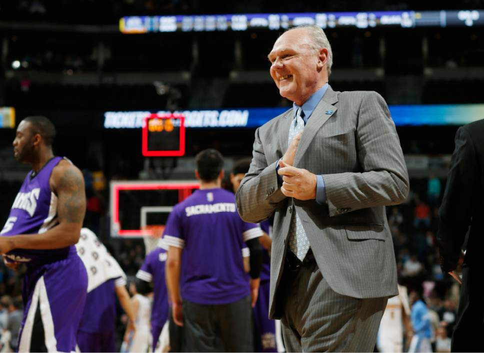 FILE - In this Saturday, April 2, 2016, file photo, Sacramento Kings head coach George Karl smiles as he walks off the court after facing the Denver Nuggets in an NBA basketball game in Denver. Karl has penned a book on his career as an NBA head coach in four cities. (AP Photo/David Zalubowski, File)