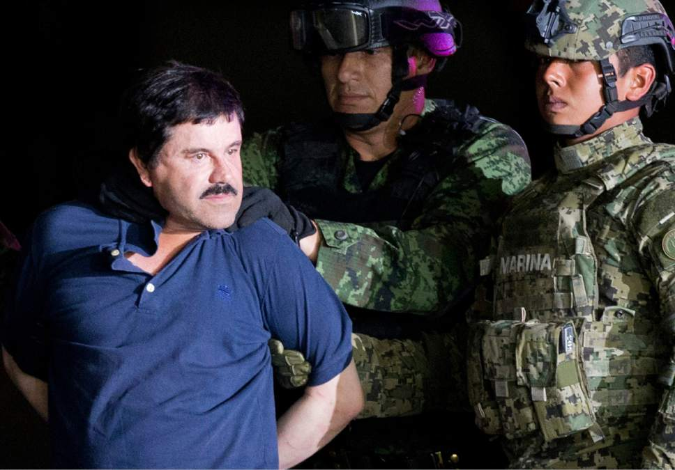 """FILE - In this Jan. 8, 2016 file photo, a handcuffed Joaquin """"El Chapo"""" Guzman is made to face the press as he is escorted to a helicopter by Mexican soldiers and marines at a federal hangar in Mexico City. Mexico's most notorious cartel kingpin who twice made brazen prison escapes and spent years on the run as the country's most wanted man, was extradited to the United States on Thursday, Jan. 19, 2017, to face drug trafficking and other charges. (AP Photo/Eduardo Verdugo, File)"""