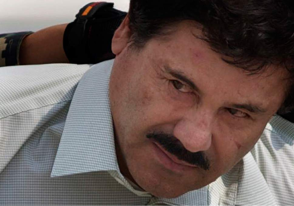 """FILE - In this Feb. 22, 2014 file photo, Joaquin """"El Chapo"""" Guzman is escorted to a helicopter in handcuffs by Mexican navy marines at a navy hanger in Mexico City. Mexico's government said on Thursday, Jan. 19, 2017, that it has extradited drug lord Joaquin """"El Chapo"""" Guzman to the U.S. to face drug trafficking and other charges. (AP Photo/Eduardo Verdugo, File)"""