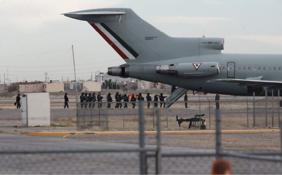 """Police board Mexican Air Force plane after the extradition of drug lord Joaquin """"El Chapo"""" Guzman in Ciudad Juarez, Mexico, Thursday, Jan. 19, 2017. Mexico's Foreign Relations Department announced Guzman was handed over to U.S. authorities for transportation to the U.S. on Thursday, the last day of President Barack Obama's administration and a day before Donald Trump is to be inaugurated. (AP Photo/Christian Torres)"""