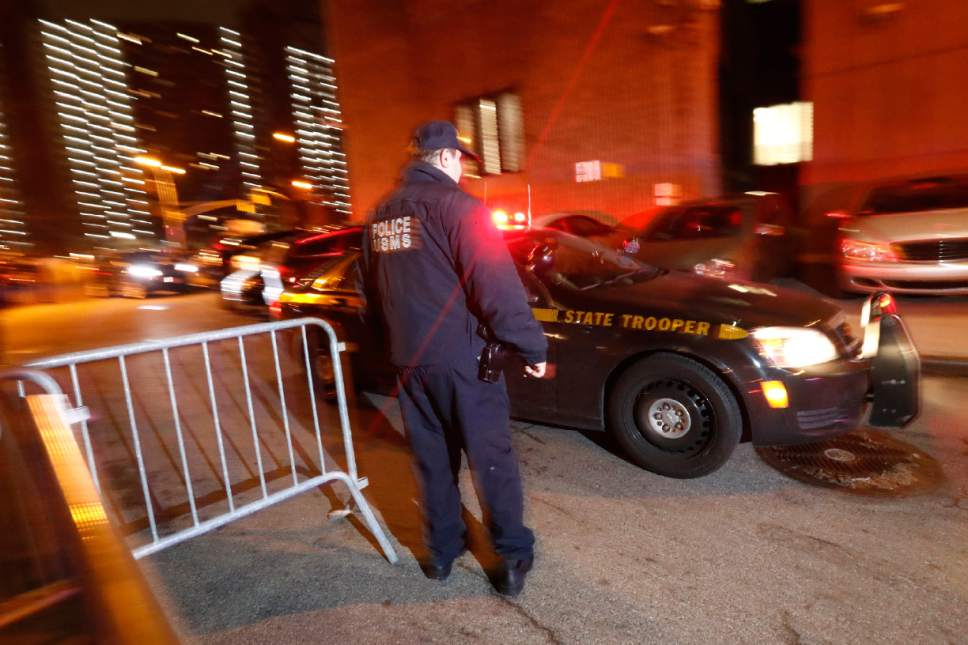 """An official looks on as a New York State Police vehicle, part of a motorcade carrying Mexican drug kingpin Joaquin """"El Chapo"""" Guzman, arrives at the Metropolitan Correctional Center in New York, Thursday, Jan. 19, 2017. The infamous drug kingpin who twice escaped from maximum-security prisons in Mexico was extradited at the request of the U.S. to face drug trafficking and other charges, and landed in New York late Thursday, a federal law enforcement official said. (AP Photo/Julio Cortez)"""