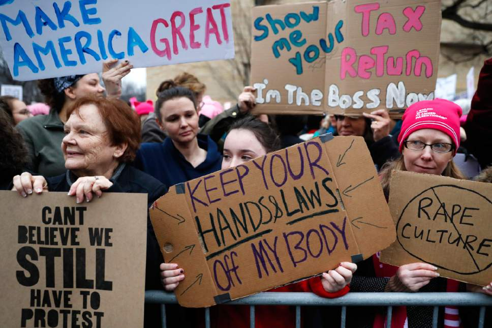 Lily Donahue of Wappingers Falls, N.Y., center, holds a sign along the barricades at the Women's March on Washington during the first full day of Donald Trump's presidency, Saturday, Jan. 21, 2017 in Washington.  (AP Photo/John Minchillo)