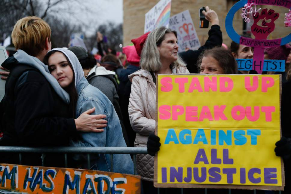 Protestors wait for speakers to begin their speeches in the cold along the barricades at the Women's March on Washington during the first full day of Donald Trump's presidency, Saturday, Jan. 21, 2017 in Washington. Organizers of the Women's March on Washington expect more than 200,000 people to attend the gathering. Other protests are expected in other U.S. cities. (AP Photo/John Minchillo)