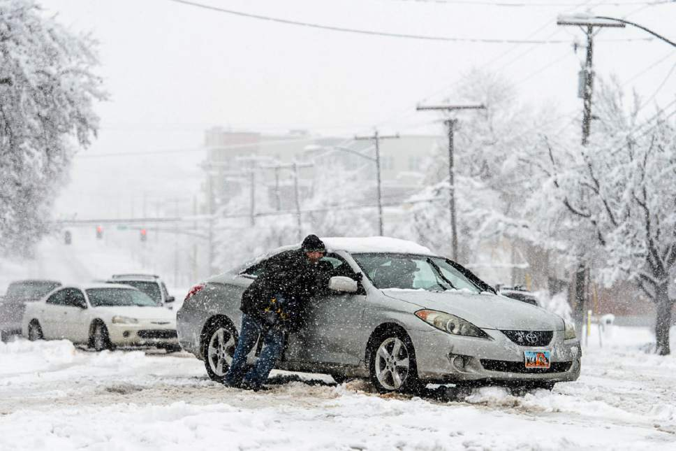 Trent Nelson     The Salt Lake Tribune People work to get a car unstuck at South Temple and 400 East as a snowstorm hits Salt Lake City, Saturday January 21, 2017.