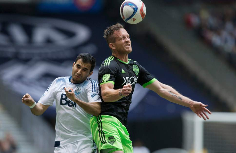 Seattle Sounders' Chad Barrett, right, out-jumps Vancouver Whitecaps' Steven Beitashour to get his head on the ball during the first half of an MLS soccer game in Vancouver, British Columbia, on Saturday, May 16, 2015. (Darryl Dyck/The Canadian Press via AP)
