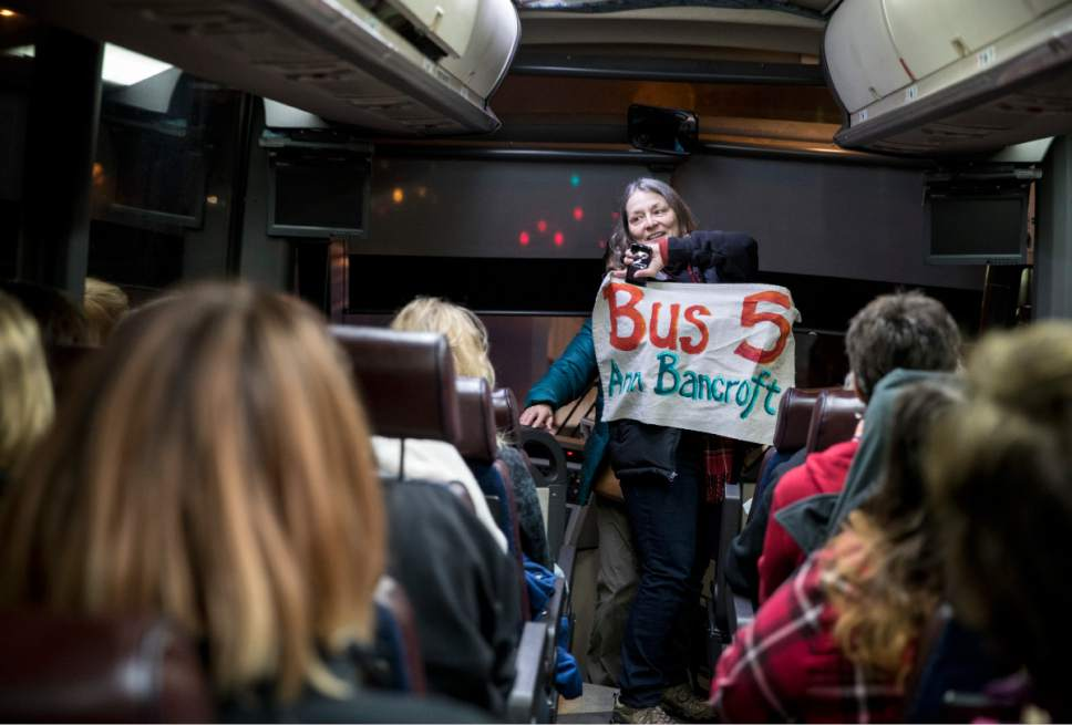 Deborah Capouch holds up the bus sign that included it's name, Anne Bancroft, before it hit the road for the Women's March on Washington early Friday morning, Jan. 20, 2016, in Minneapolis, Minn. The eight buses chartered from Minnesota were all named after prominent Minnesota women. (Renee Jones Schneider/Star Tribune via AP)