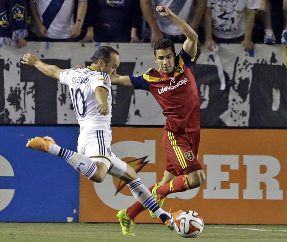 Real Salt Lake defender Tony Beltran covers as Los Angeles Galaxy midfielder Landon Donovan attacks in the first half of an MLS soccer game in Carson, Calif., Saturday, March 8, 2014.  Real Salt Lake won, 1-0. (AP Photo/Reed Saxon)