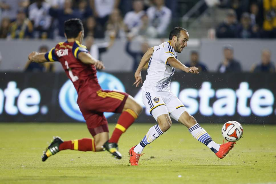 Los Angeles Galaxy's Landon Donovan, right, scores a goal past Real Salt Lake's Tony Beltran, left, during the second half of their second leg MLS soccer Western Conference playoff series game, in Carson, Calif., Sunday, Nov. 9, 2014. (AP Photo/Danny Moloshok)