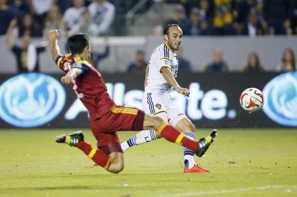 Los Angeles Galaxy's Landon Donovan scores a goal past Real Salt Lake's Tony Beltran, left, during the second half of their second leg MLS soccer Western Conference playoff series game, in Carson, Calif., Sunday, Nov. 9, 2014. (AP Photo/Danny Moloshok)