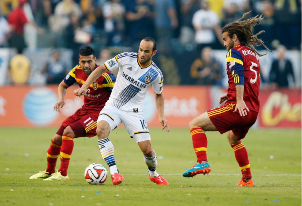 Los Angeles Galaxy's Landon Donovan, center, controls the ball between Real Salt Lake's Javier Morales, left, and Kyle Beckerman, right, during the first half of an MLS soccer Western Conference playoff series game, Sunday, Nov. 9, 2014, in Carson, Calif., Sunday, Nov. 9, 2014. (AP Photo/Danny Moloshok)
