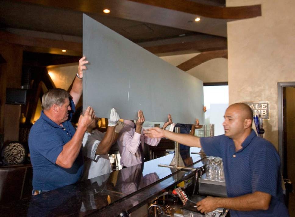"Paul Fraughton  |  Tribune file photo  Moshen Asgari, right, supervises the removal of the ""Zion curtain"" from the bar at his Vuda Bar and Winery in Draper. A new poll says that most Utahns would like to do away with the so-called ""Zion Curtains."""