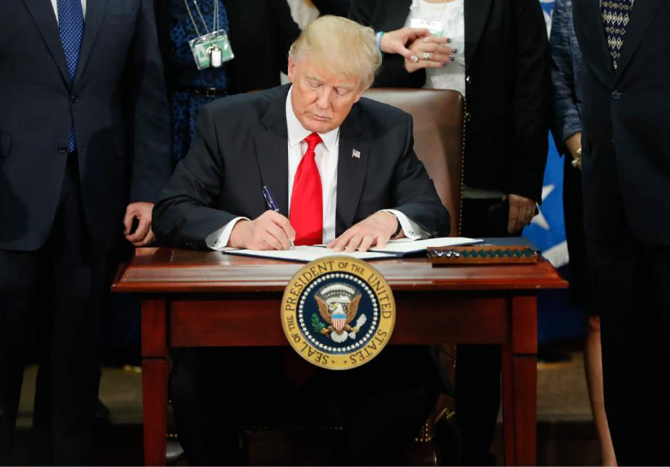 In this Jan. 25, 2017, photo, President Donald Trump signs an executive order for border security and immigration enforcement improvements at the Department of Homeland Security in Washington. Immigration to the United States has come in swells and dips over the past two-plus centuries, driven by shifts in U.S. policy, the mood in the country and world events.   (AP Photo/Pablo Martinez Monsivais)