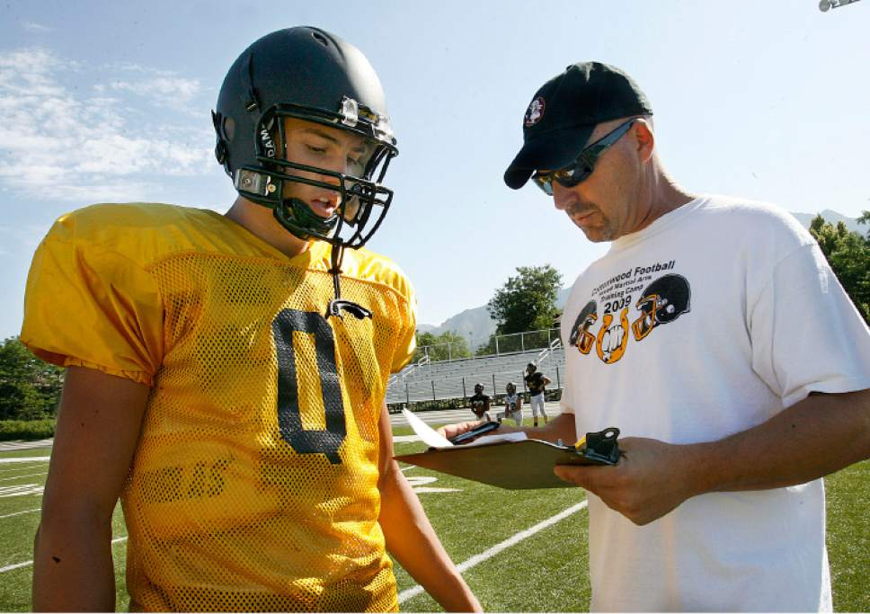 Scott Sommerdorf  l  The Salt Lake Tribune  Cottonwood High football coach Scott Cate calls the next play for his QB Cooper Bateman (left) to run during practice in Murray on Thursday, August 12, 2010.