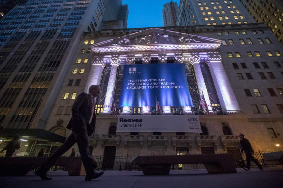 FILE - In this Tuesday, Oct. 25, 2016, file photo, a pedestrian walks past the New York Stock Exchange, in lower Manhattan. Global stock markets fell Monday, Jan. 30, 2017, after President Donald Trump's decision to impose a travel ban on seven Muslim-majority countries. Airlines and technology companies took some of the largest losses. Rite Aid is falling after Walgreens lowered the price it will pay to buy the company. (AP Photo/Mary Altaffer, File)
