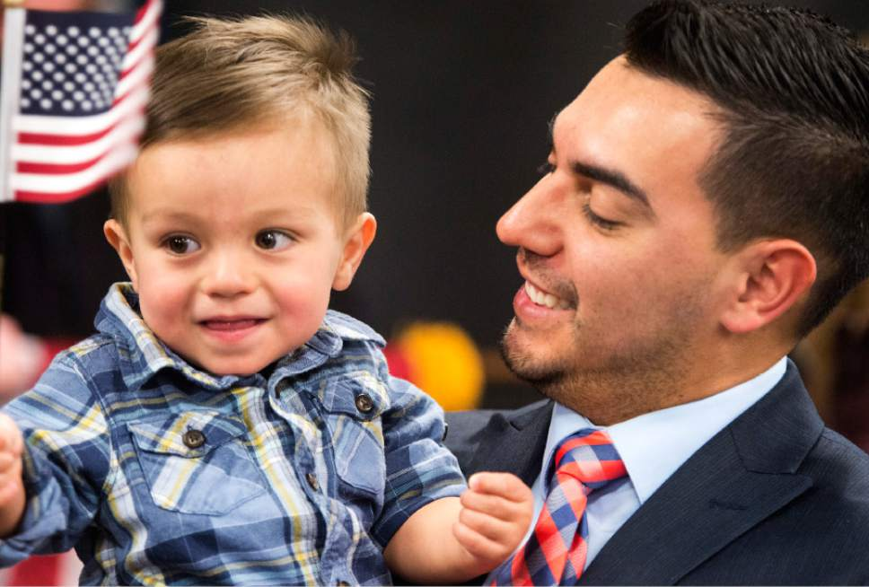Rick Egan  |  The Salt Lake Tribune Jeison Carrillo, from Costa Rica, holds his son Greyson, after his naturalization ceremony. Carrillo and 29 other citizenship candidates from 14 countries took the Oath of Allegiance to become U.S. citizens at the University of Utah College of Social Work Okazaki Community Meeting Room, Monday, January 30, 2017.