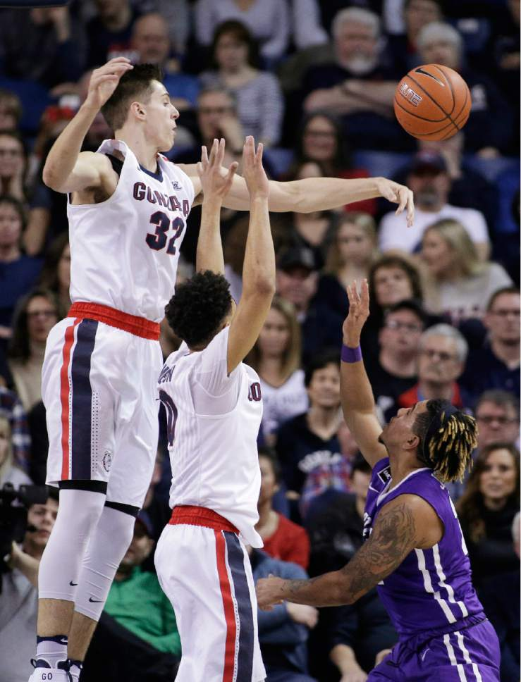 Gonzaga forward Zach Collins (32) blocks a shot by Portland guard Jazz Johnson, right, next to teammate guard Silas Melson during the first half of an NCAA college basketball game in Spokane, Wash., Saturday, Jan. 21, 2017. (AP Photo/Young Kwak)