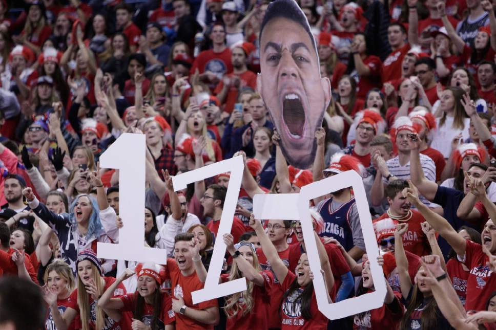 """Fans in the Gonzaga student section hold""""17-0"""" signs, Gonzaga's overall season record, and a large printed cutout of Gonzaga guard Nigel Williams-Goss during the second half of the team's NCAA college basketball game against Saint Mary's in Spokane, Wash., Saturday, Jan. 14, 2017. Gonzaga won 79-56. (AP Photo/Young Kwak)"""