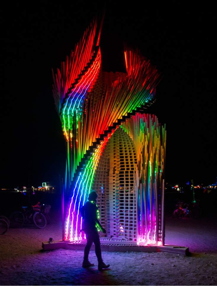"Rick Egan  |  The Salt Lake Tribune  ""Tangential Dreams"" by Arthur Mamou-Mani, London, United Kingdom,at the Burning Man Festival, in the Black Rock Desert, 100 miles north of Reno, NV, Friday, September 2, 2016. Tangential Dreams is a climbable tower made from off-the-shelf timber and digitally designed via algorithmic rules. The pieces are lit by LED strips during the night."