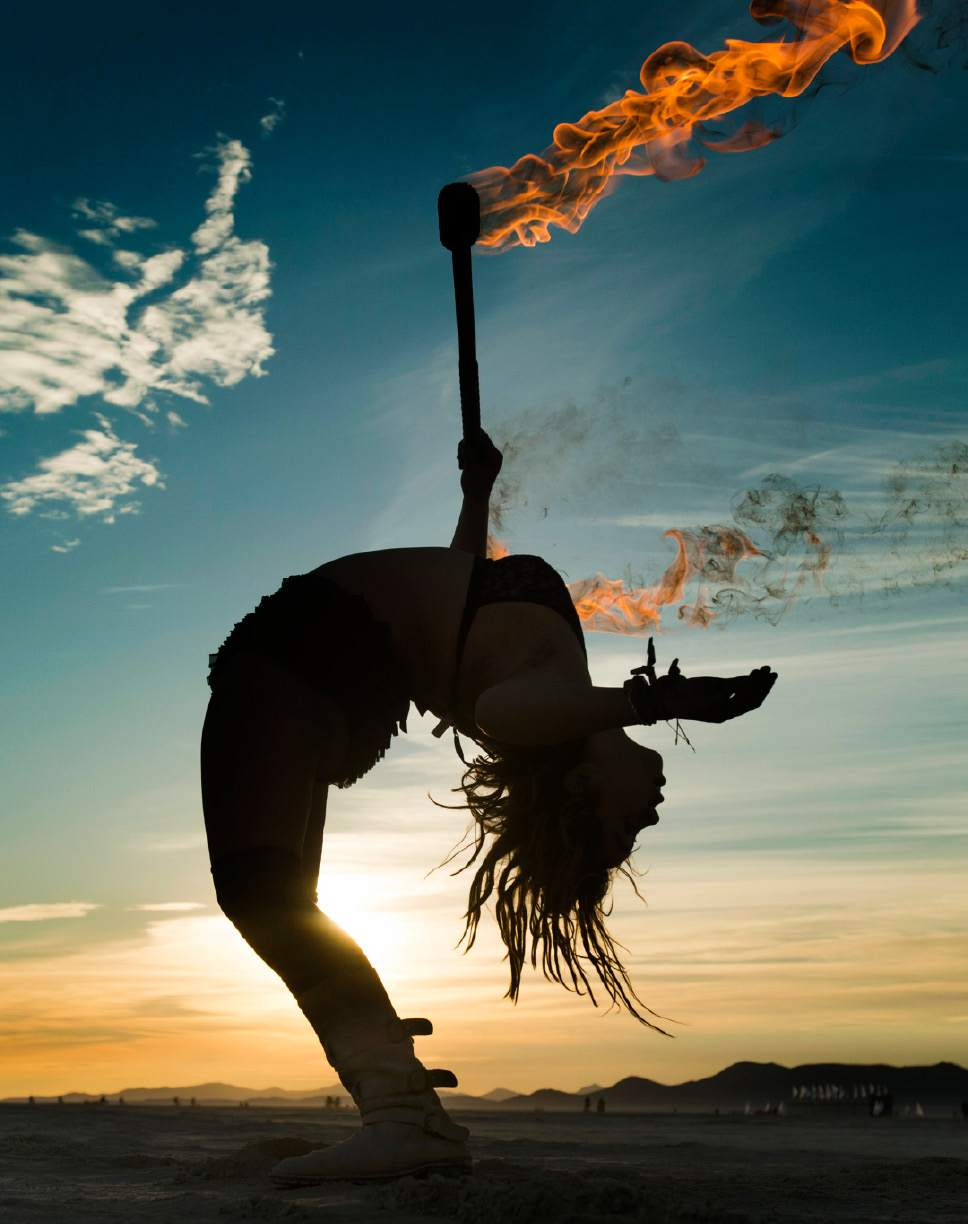 Rick Egan  |  The Salt Lake Tribune  Darlene VonMaschmeyer, Santa Cruz, CA, dances with fire at sunrise, at the Burning Man Festival ,in the Black Rock Desert, 100 miles north of Reno, NV, Saturday, September 3, 2016.