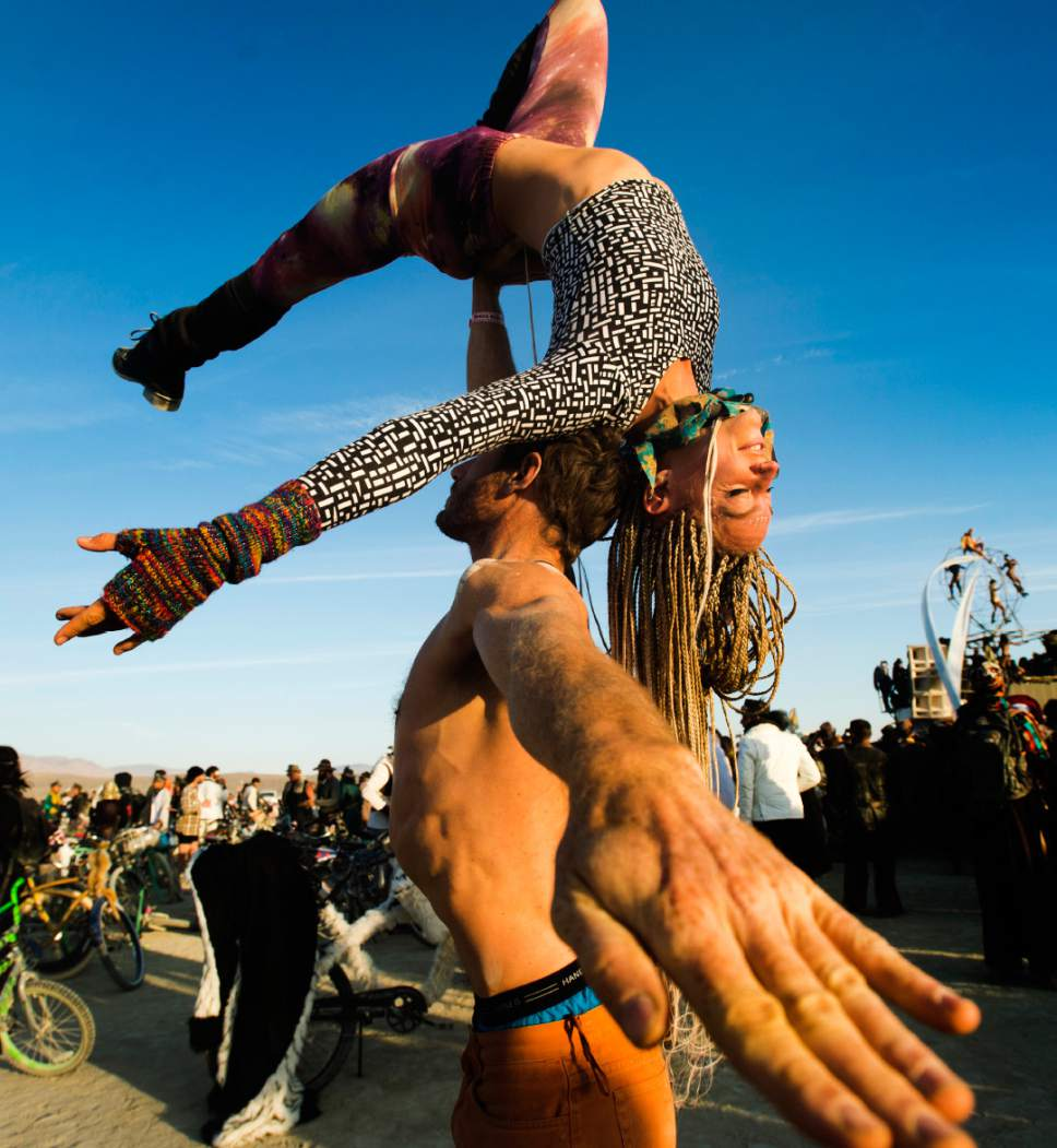 Rick Egan  |  The Salt Lake Tribune  Adam Hiner, and Sae Bluff, San Diego, CA, do some acrobatics, at the Burning Man Festival, in the Black Rock Desert, 100 miles north of Reno, NV, Saturday, September 3, 2016.