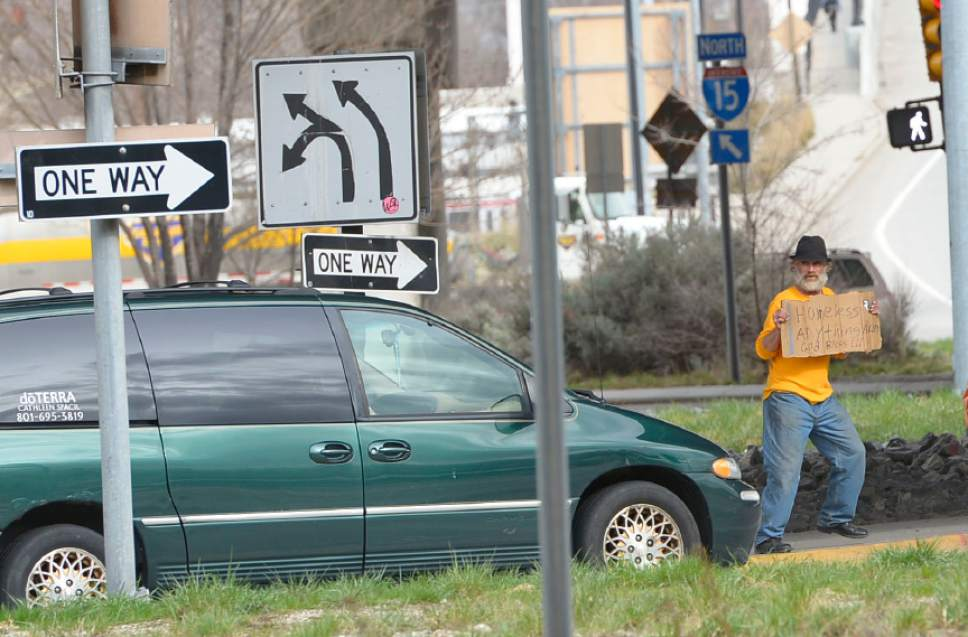 Leah Hogsten  |  Tribune file photo  Lee McCashland panhandles along 400 South in this 2014 photo. A bill aimed at prohibiting panhandling on high-speed highways is framed as a pedestrian and traffic safety measure.