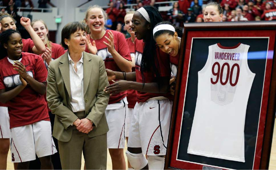 FILE - In this Dec. 14, 2013, file photo, Stanford coach Tara VanDerveer, second from left, is presented a framed jersey in recognition of her 900 career wins after the team's NCAA college basketball game against Gonzaga in Stanford, Calif. On Friday night when No. 8 Stanford hosts USC, Vanderveer is poised to become just the second NCAA women's coach to enter the 1,000 wins club, alongside the late Pat Summitt. (AP Photo/Ben Margot, File)