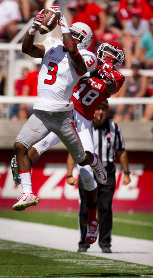 Trent Nelson  |  The Salt Lake Tribune Fresno State Bulldogs wide receiver Josh Harper (3) pulls in a pass in front of Utah Utes defensive back Eric Rowe (18) as Utah hosts Fresno State, college football at Rice-Eccles Stadium Saturday September 6, 2014.