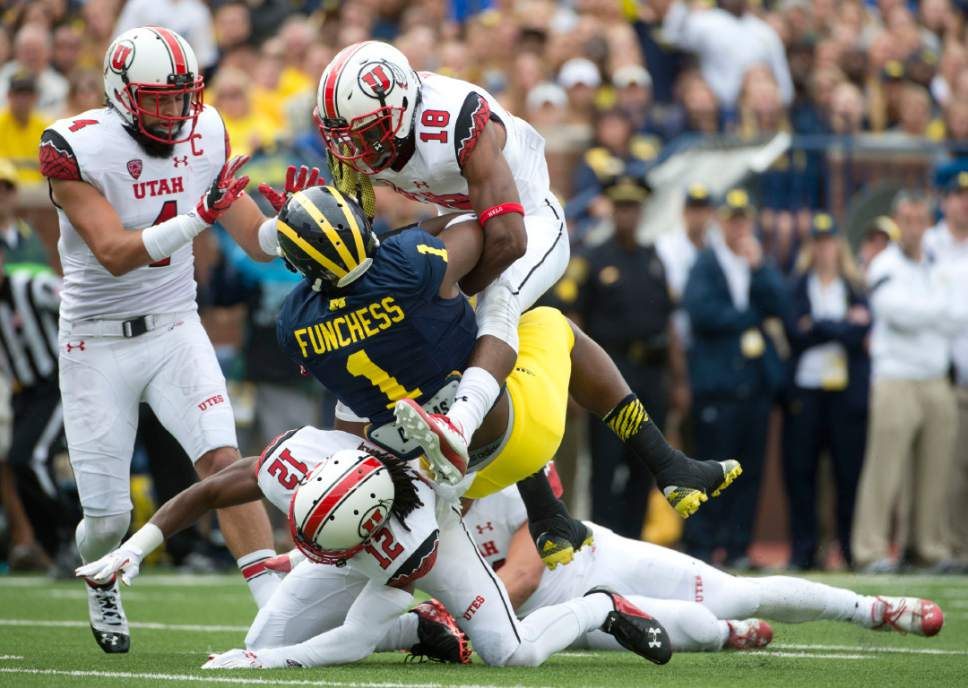 Jeremy Harmon  |  The Salt Lake Tribune  Utah's Brian Blechen (4), Eric Rowe (18) and Justin Thomas (12) tackle Michigan's Devin Funchess as the Utes face the Wolverines in Ann Arbor, Saturday, Sept. 20, 2014.