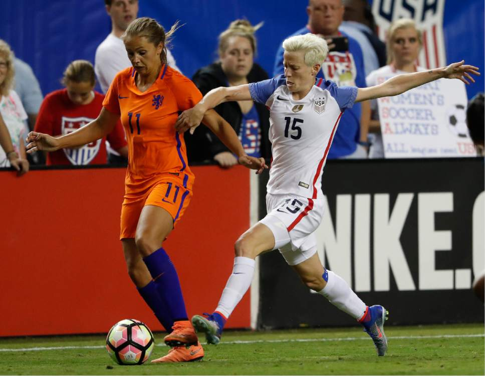 FILE - In this Sept. 18, 2016 file photo, USA's Megan Rapinoe (15) and Netherlands' Lieke Martens (11) battle for the ball in the second half of an exhibition soccer match in Atlanta. The 2015 Women's World Cup champions have been without a deal since Dec. 31. Talks were stalled when the players parted ways in late December with attorney Rich Nichols, who had been executive director of the U.S. Women's National Team Player Association since late 2014. (AP Photo/John Bazemore)
