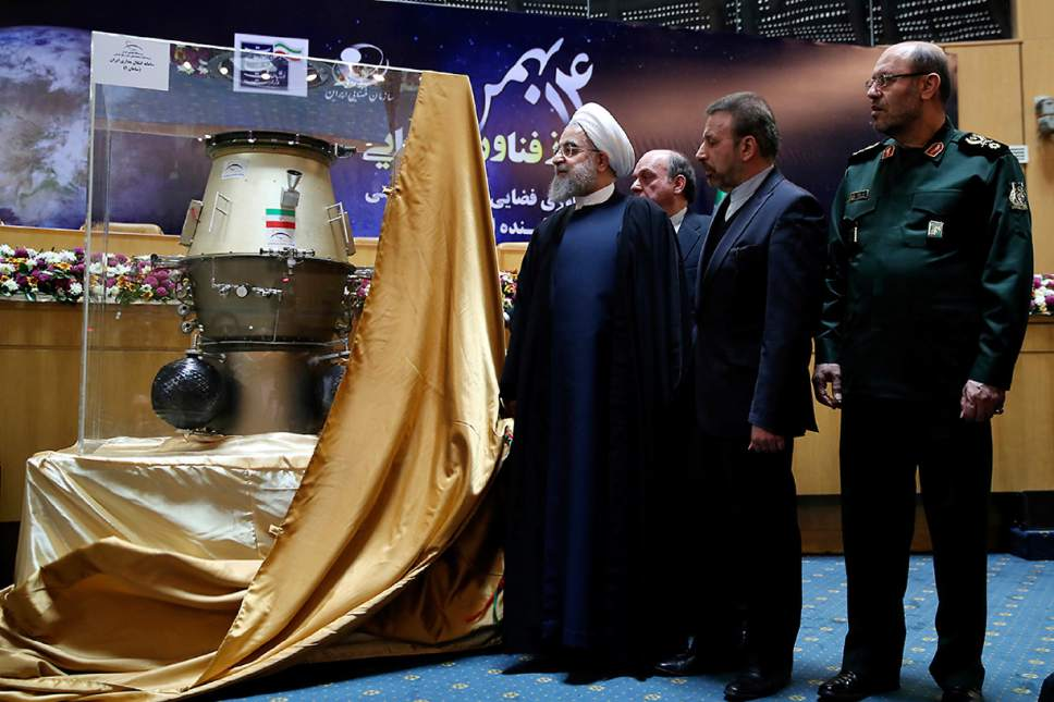 In this photo released by official website of the office of the Iranian Presidency, President Hassan Rouhani, left, visits an exhibition of Iran's latest achievements of space technology, in Tehran, Iran, Wednesday, Feb. 1, 2017. President Hassan Rouhani has lashed out at the recent executive order by U.S. president Donald Trump to suspend immigration and visa processes for nationals from seven majority-Muslim countries, including Iran. Minister of Communications and Information Technology Mahmoud Vaezi, center, and Defense Minister Hossein Dehghan accompany Rouhani. (Iranian Presidency Office via AP)