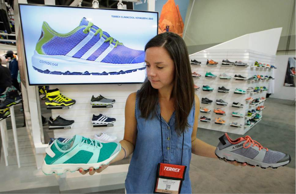 Exhibitor Kristen Bujold, of Adidas Outdoor, holds the Adidas Terrex Climacool Voyager, at their exhibit during the Outdoor Retailer show Thursday, Aug. 4, 2016, in Salt Lake City. A wide array of clothing, gear and equipment specifically designed for women outdoor adventurers is on display at the summer version of the world's largest outdoor gear show for retailers that brings thousands of  people to Salt Lake City. (AP Photo/Rick Bowmer)