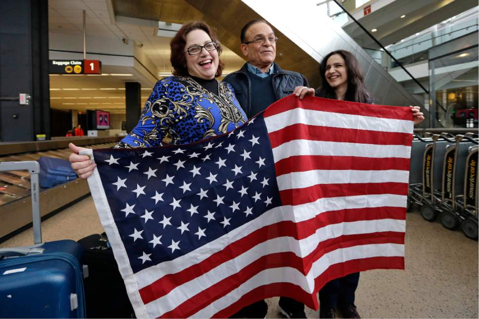 Jayne Novak, left, smiles as she stands with her husband, Allen Novak, newly-arrived from Iran, and their daughter Nikta, as they stand with a flag and pose for cameras Monday, Feb. 6, 2017, at Seattle Tacoma International Airport in SeaTac, Wash. Allen Novak joined his family, of Silverdale, Wash., on a conditional resident visa. Washington Governor Jay Inslee, Attorney General Bob Ferguson, and Port of Seattle Commissioner President Tom Albro joined family members Monday to welcome another immigrant, Isahaq Ahmed Rabi, who was blocked from entry last week due to President Donald Trump's immigration order. (AP Photo/Elaine Thompson)