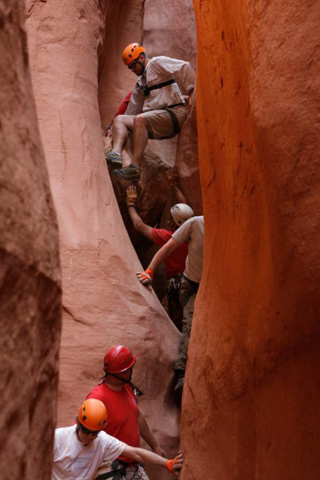 Francisco Kjolseth  |  The Salt Lake Tribune Using a number of techniques, the group makes its way down a slot canyon in Grand Staircase National Monument making sure to maintain a slow pace so no one gets hurt in such a cramped space.