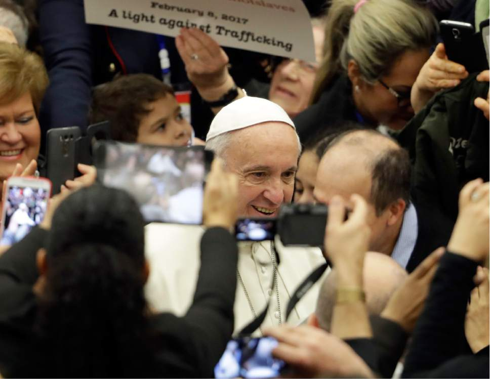 Pope Francis is surrounded by faithful, including one holding a poster against human trafficking, during his weekly general audience in Paul VI Hall, at the Vatican, Wednesday, Feb. 8, 2017. The Vatican has been hosting a conference on human trafficking as part of Francis' efforts to crack down on trafficking in humans and organs. (AP Photo/Andrew Medichini)