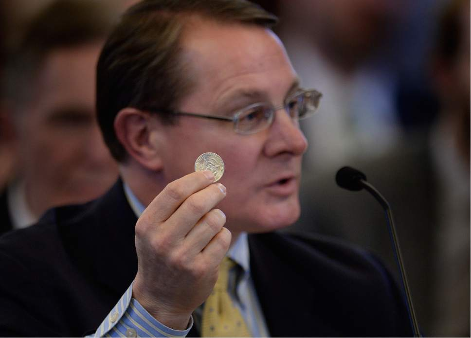 Scott Sommerdorf   |  The Salt Lake Tribune   Rep. Ken Ivory, R-West Jordan, holds up a Kennedy 50 cent piece during his presentation of his bill HB224 - Specie Legal Tender Amendments - in a House committee meeting, Wednesday, February 8, 2017.