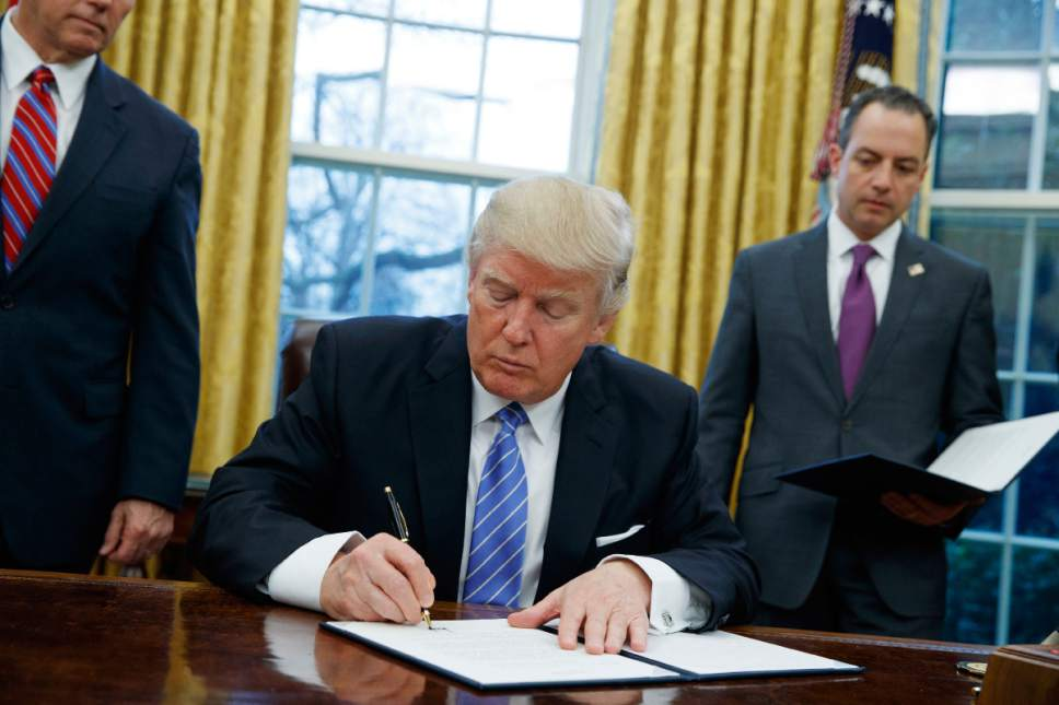 FILE - In this Jan. 23, 2017, file photo, President Donald Trump signs an executive order to withdraw the U.S. from the 12-nation Trans-Pacific Partnership trade pact agreed to under the Obama administration in the Oval Office of the White House in Washington. (AP Photo/Evan Vucci, File)