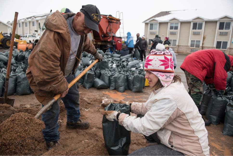 Lennie Mahler  |  The Salt Lake Tribune  Volunteers Celestno Ramirez and Laura Gough fill bags with sand to block flooding in Garden City, Utah, Friday, Feb. 10, 2017.