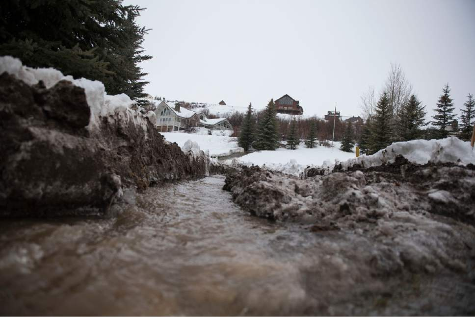 Lennie Mahler  |  The Salt Lake Tribune  Water flows from a canal onto the street in the Harbor Village neighborhood in Garden City, Utah, Friday, Feb. 10, 2017.
