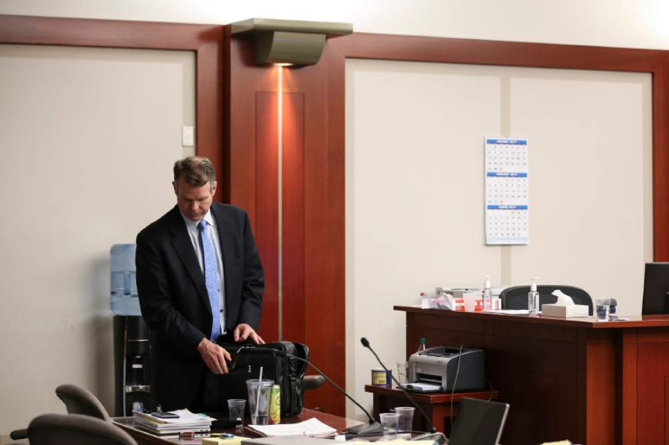 John Swallow packs his bag at the end of the fourth day of his public corruption trial at the Matheson Courthouse in Salt Lake City on Friday, Feb. 10, 2017.