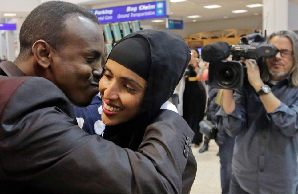 Abdisellam Hassen Ahmed, a Somali refugee who had been stuck in limbo after President Donald Trump temporarily banned refugee entries, kisses his wife Nimo Hashi, after arriving at Salt Lake International Airport, Friday, Feb. 10, 2017, in Salt Lake City. Ahmed meet his 2-year-old daughter, Taslim, for the first time. Ahmed is among a wave of refugees around the country making belated arrivals after their trips were cancelled several weeks ago after Trump's executive order. (AP Photo/Rick Bowmer)